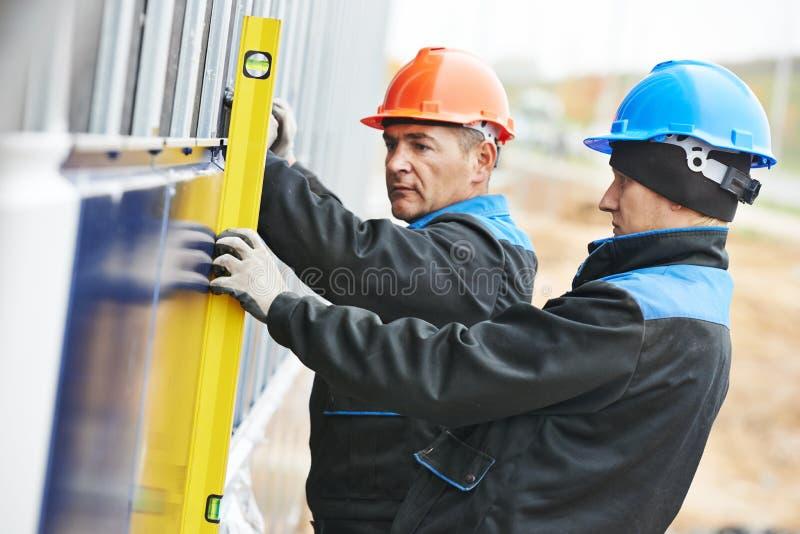 Trabajador del yesero de la fachada del constructor con el nivel imagen de archivo libre de regalías