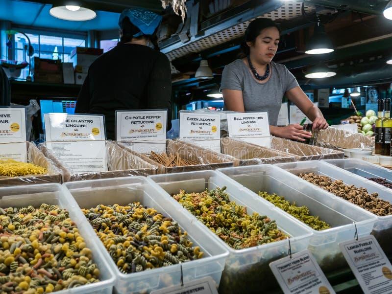 Trabajador detrás de la exhibición de las pastas, mercado público del lugar de Pike, Seattle imagen de archivo libre de regalías