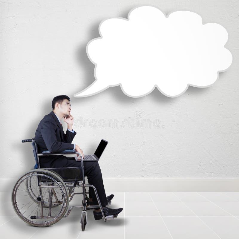 Trabajador discapacitado que mira la burbuja del discurso fotografía de archivo libre de regalías