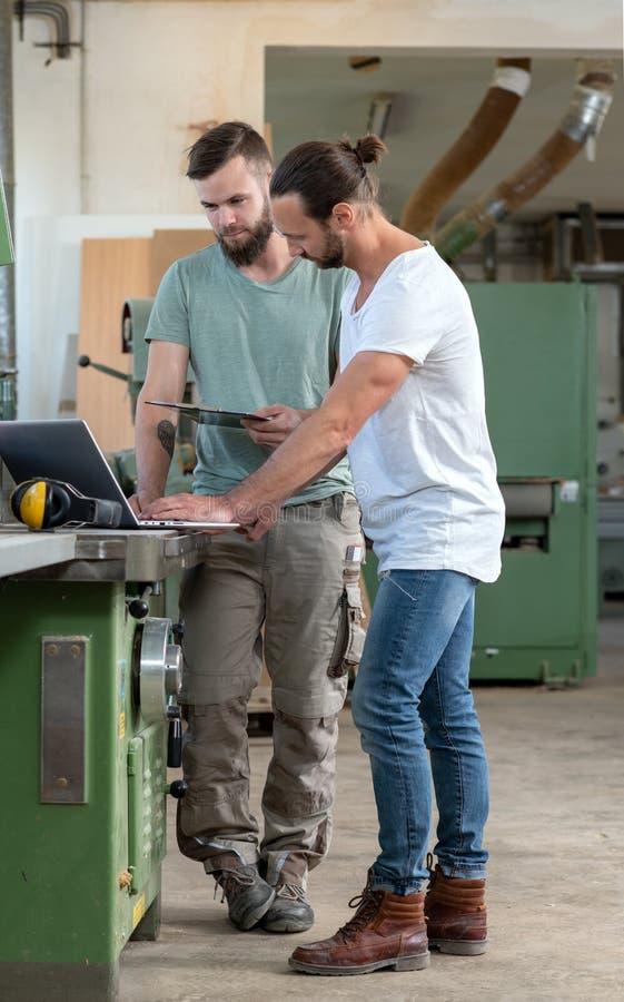 Trabajador dos en el taller de un carpintero con el ordenador y el tablero fotos de archivo