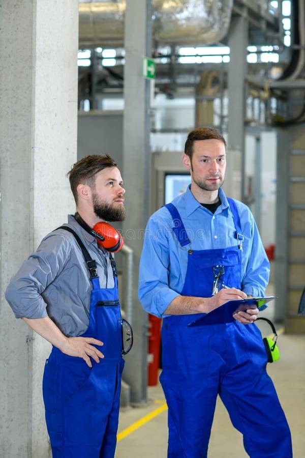 Trabajador dos en planta industrial fotografía de archivo libre de regalías