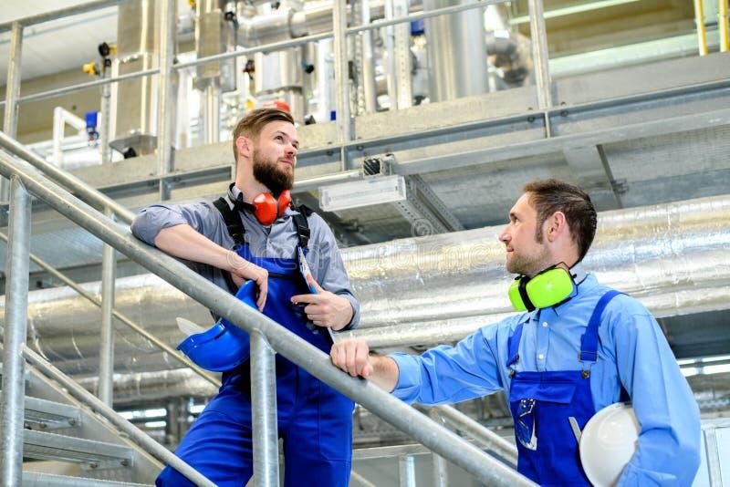 Trabajador dos en planta industrial foto de archivo