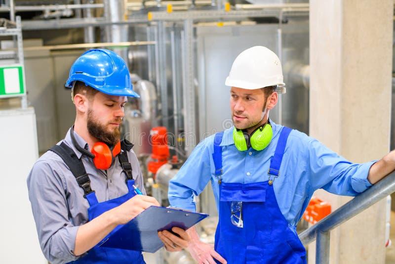 Trabajador dos en planta industrial imagen de archivo