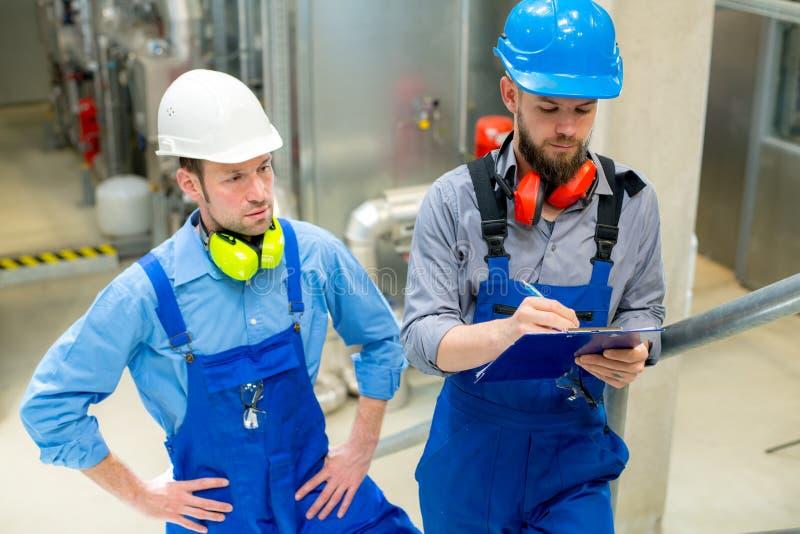 Trabajador dos en planta industrial fotos de archivo