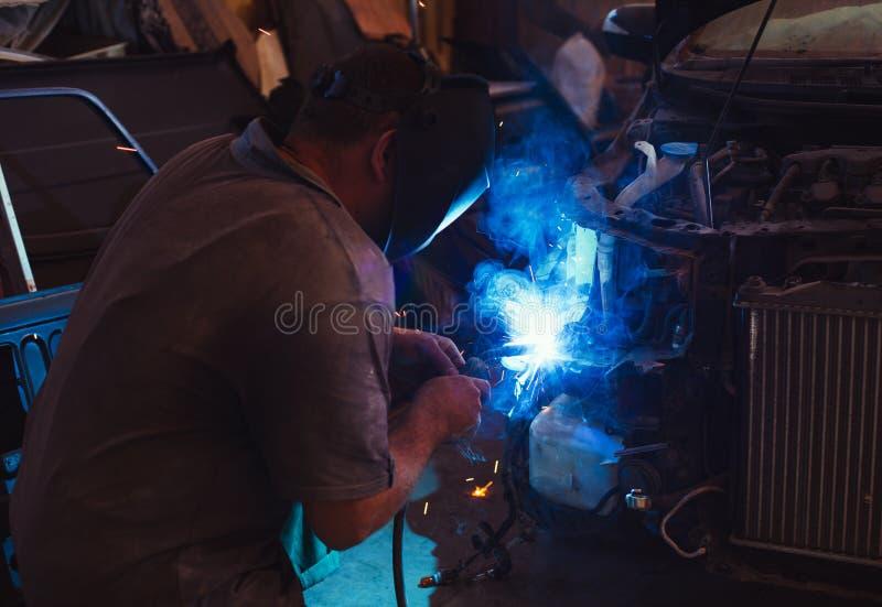 Trabajador en detalle de la reparación del casco en servicio auto del coche fotografía de archivo libre de regalías