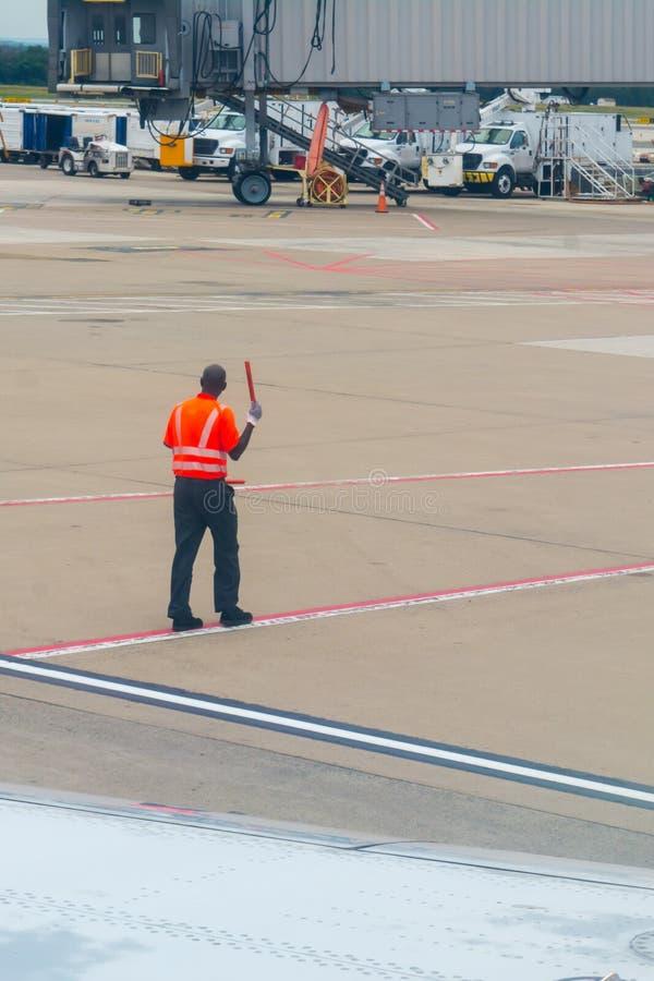 Trabajador en el aeropuerto que viste una chaqueta roja de la seguridad foto de archivo libre de regalías