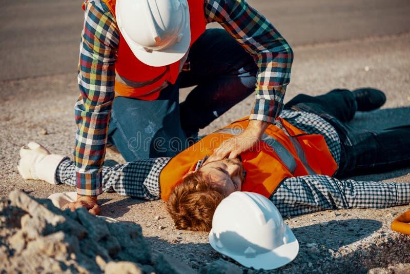 Trabajador en el casco blanco que comprueba funciones de la vida de un hombre herido fotografía de archivo libre de regalías