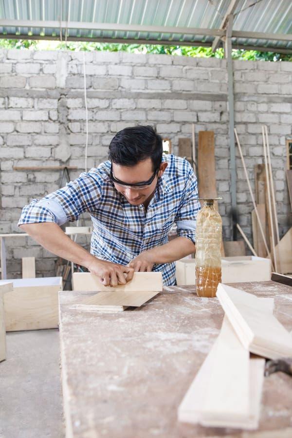 Trabajador en el espacio de trabajo del carpintero que aplica el vinilo de madera en un tablero u foto de archivo