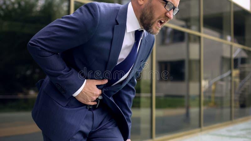 Trabajador en el traje que sufre del dolor de estómago, dolor abdominal, gastroenteritis fotos de archivo libres de regalías