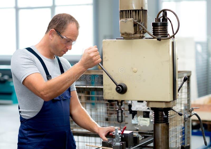 Trabajador en fábrica usando la máquina del taladro fotografía de archivo libre de regalías