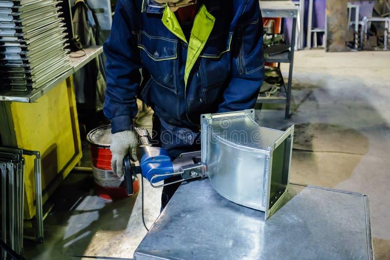 Trabajador en la instalación metalúrgica de la planta remaches en la pieza para los conductos de la construcción usando remachado foto de archivo