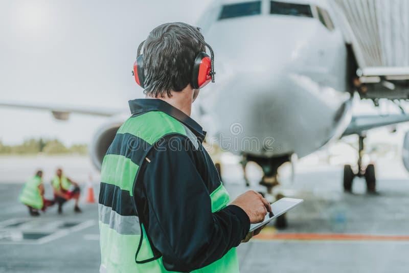 Trabajador en los auriculares rojos que miran el avión enorme fotos de archivo libres de regalías