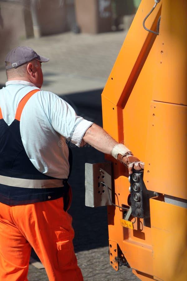Trabajador en los controles de un carro de basura imágenes de archivo libres de regalías