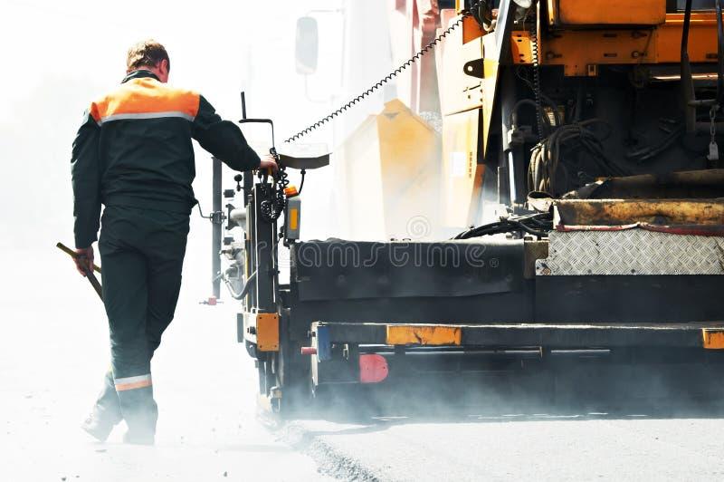 Trabajador en los trabajos de asfaltado foto de archivo libre de regalías