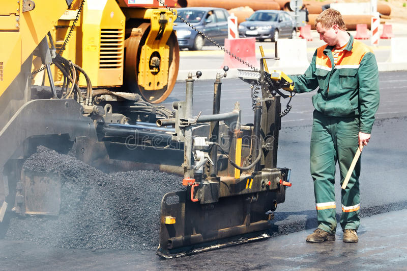 Trabajador en los trabajos de asfaltado imágenes de archivo libres de regalías