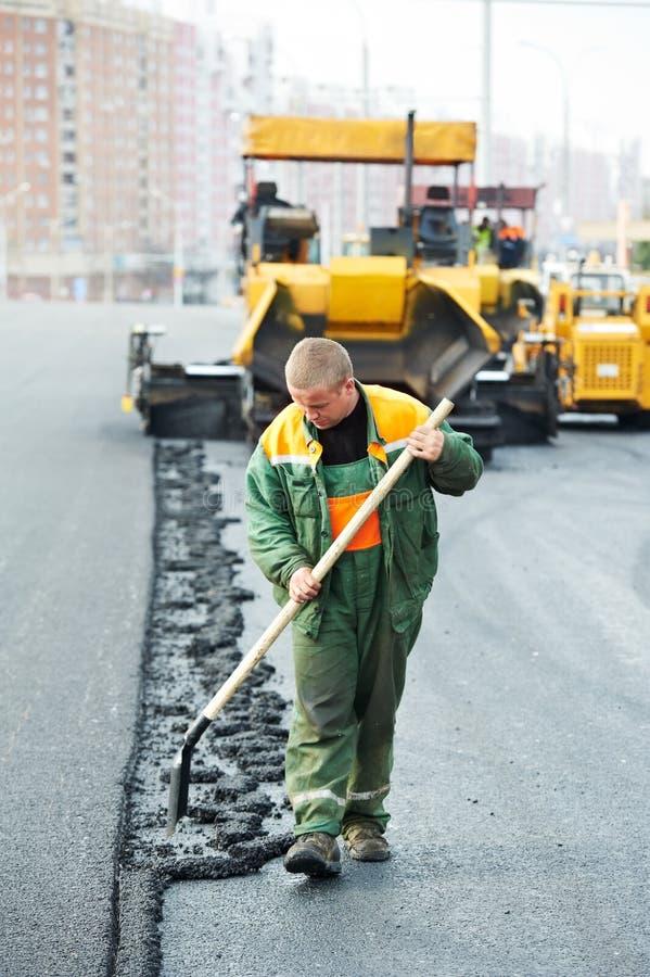 Trabajador en los trabajos de asfaltado imagen de archivo