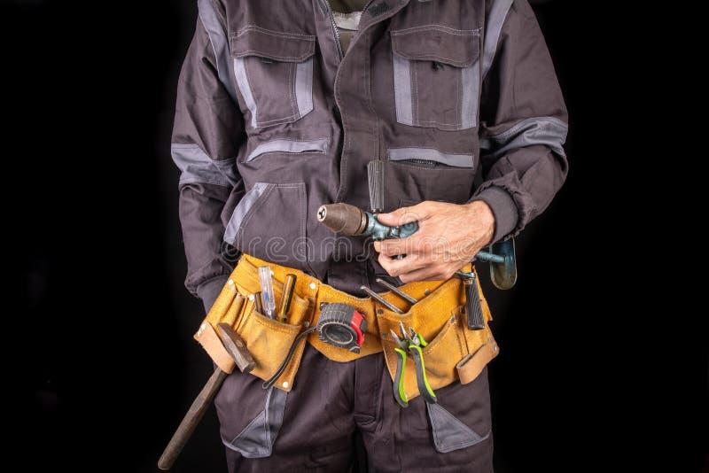 Trabajador en ropa de trabajo y correa de la herramienta Trabajador de producci?n con un taladro adentro su mano imagen de archivo