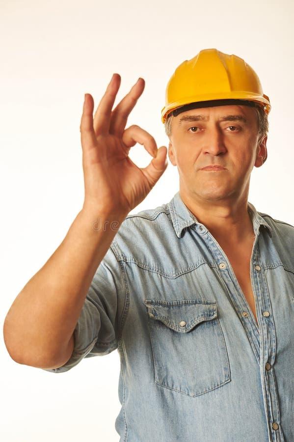 Trabajador en un casco de protección amarillo que muestra gesto ACEPTABLE foto de archivo