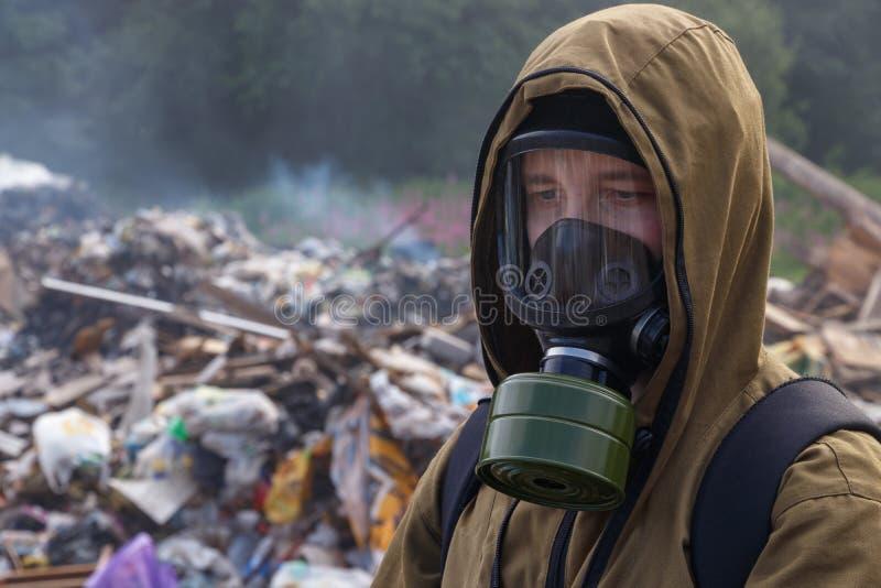Trabajador en una careta antigás en el fondo de la ruina ardiente Las muchas bolsas de plástico lanzadas hacia fuera en una desca foto de archivo