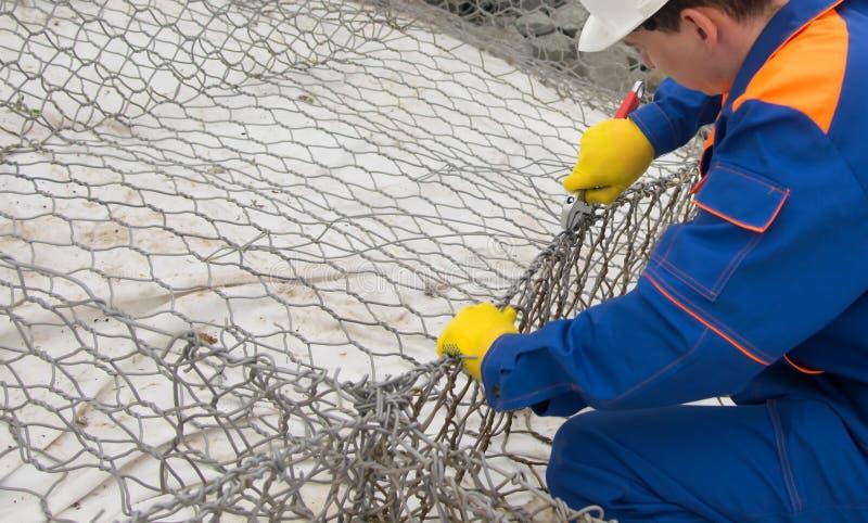 Trabajador en uniforme azul y el casco blanco que reparan la malla para las piedras de la suciedad, primer fotos de archivo libres de regalías