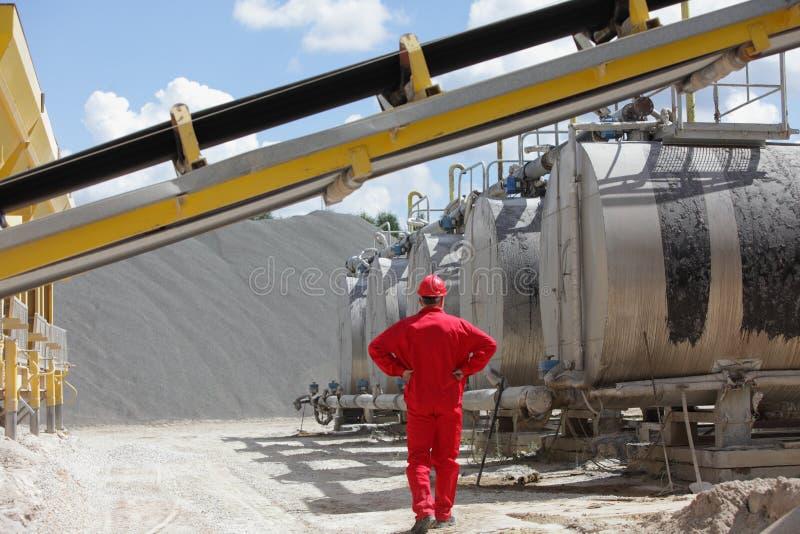 Trabajador en uniforme del rojo en los tanques con asfalto imágenes de archivo libres de regalías
