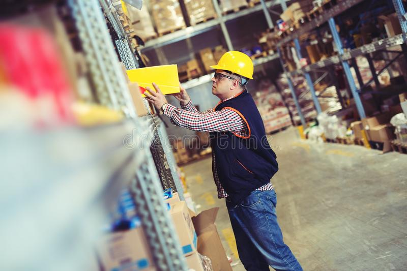 Trabajador en Warehouse que prepara las mercancías para el envío foto de archivo
