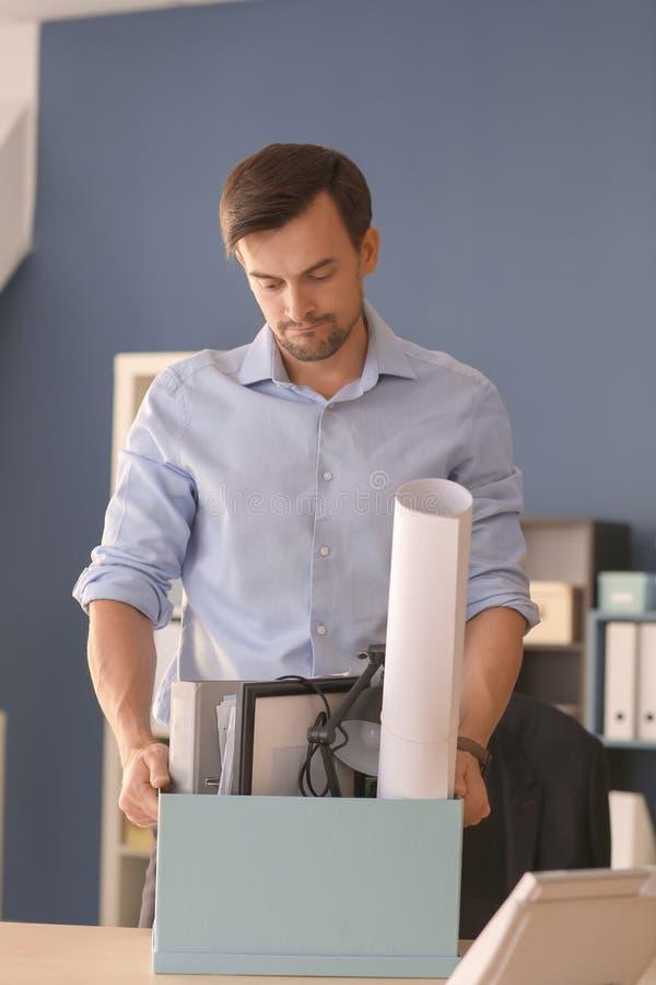 Trabajador encendido con la materia personal en oficina fotografía de archivo libre de regalías