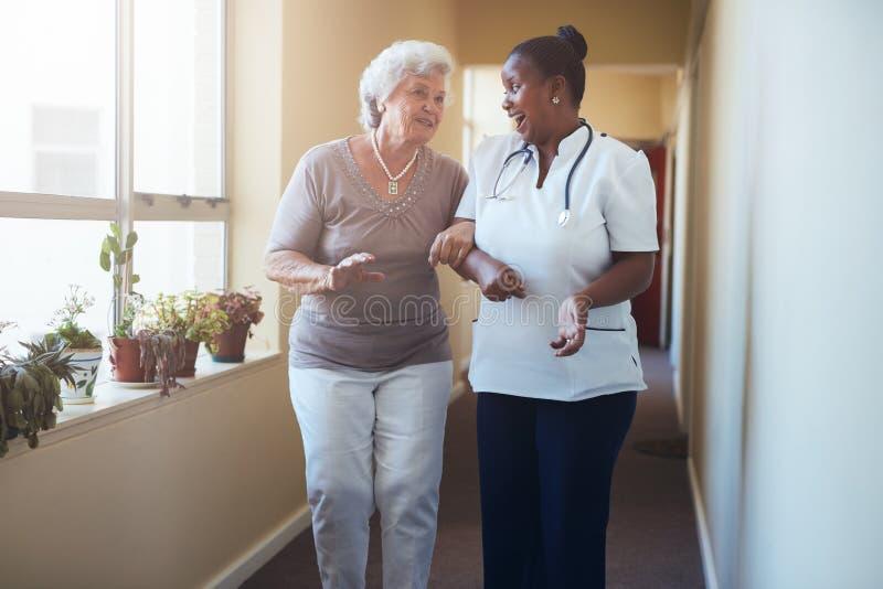 Trabajador feliz de la atención sanitaria que camina y que habla con la mujer mayor imagenes de archivo