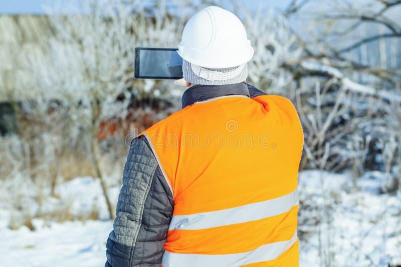 Trabajador filmado con la casa abandonada cercana de la tableta en invierno imagen de archivo libre de regalías
