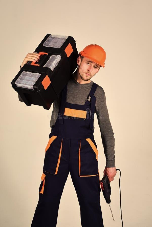 Trabajador general Reparador fuerte y atractivo, fondo gris, aislado Concepto de la manitas Hombre en guardapolvo y casco imagen de archivo