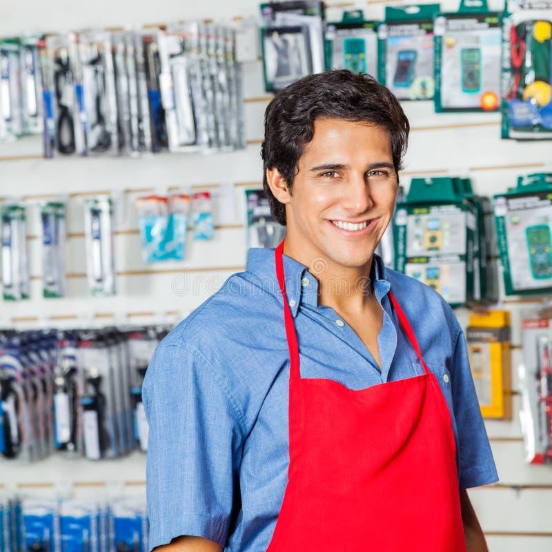 Trabajador hermoso en delantal rojo que sonríe en el hardware foto de archivo libre de regalías