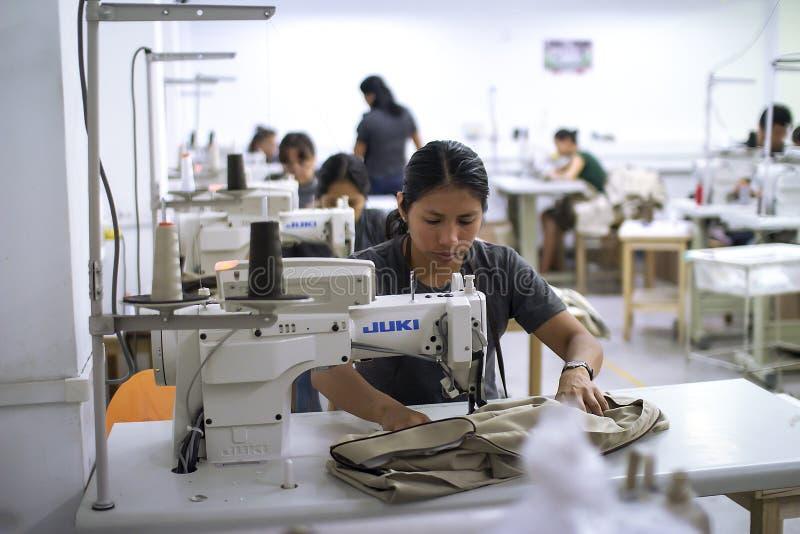 Trabajador hispánico de sexo femenino con la máquina de coser que hace alteraciones a la ropa fotos de archivo