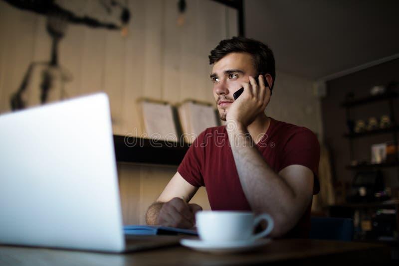 Trabajador independiente de la distancia del hombre hermoso que llama vía el teléfono móvil durante trabajo vía el ordenador port imagenes de archivo