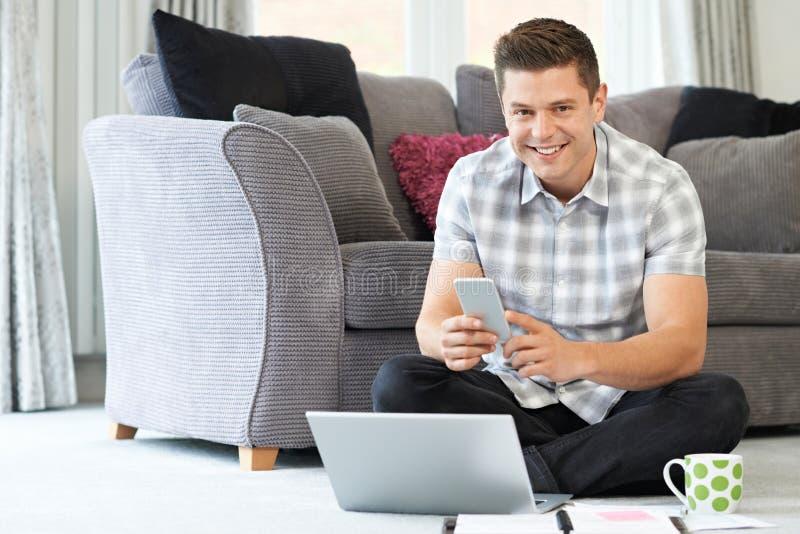 Trabajador independiente de sexo masculino que usa el ordenador portátil en casa imágenes de archivo libres de regalías