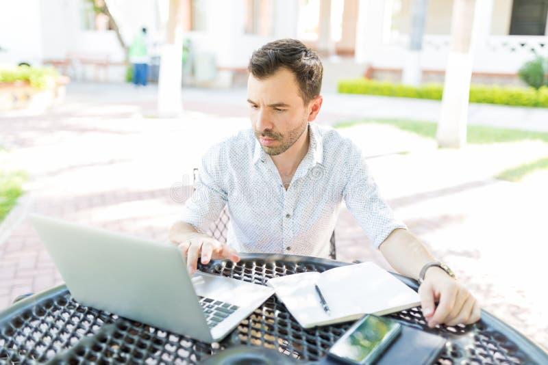 Trabajador independiente que hace proyectos en el ordenador portátil en jardín imagen de archivo libre de regalías