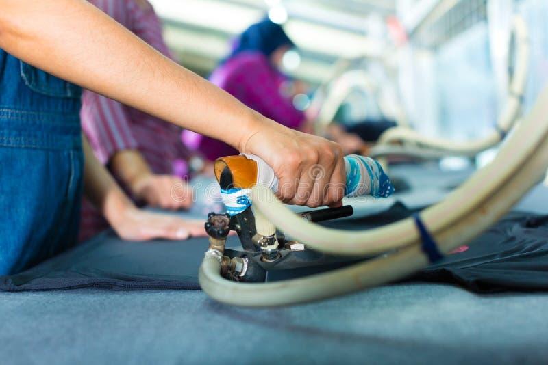 Trabajador indonesio con hierro plano en fábrica de la materia textil fotografía de archivo