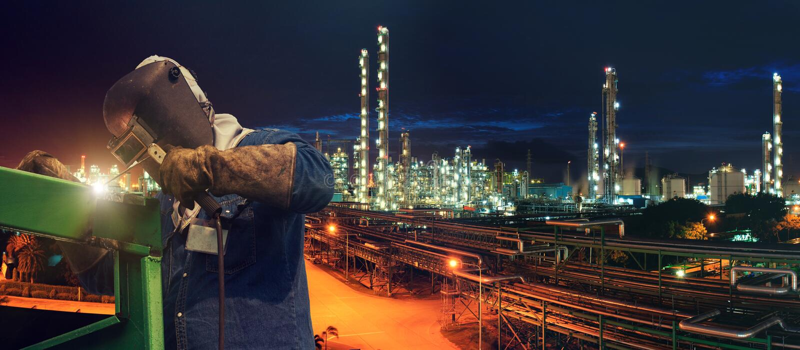 Trabajador industrial de la soldadura en la planta petroquímica fotografía de archivo libre de regalías
