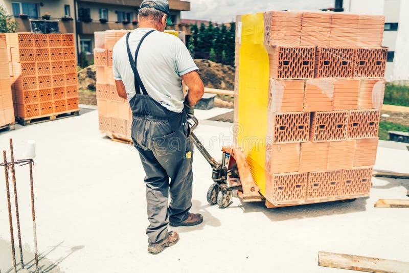 Trabajador industrial del albañil, trabajador de construcción que transporta ladrillos en emplazamiento de la obra imágenes de archivo libres de regalías