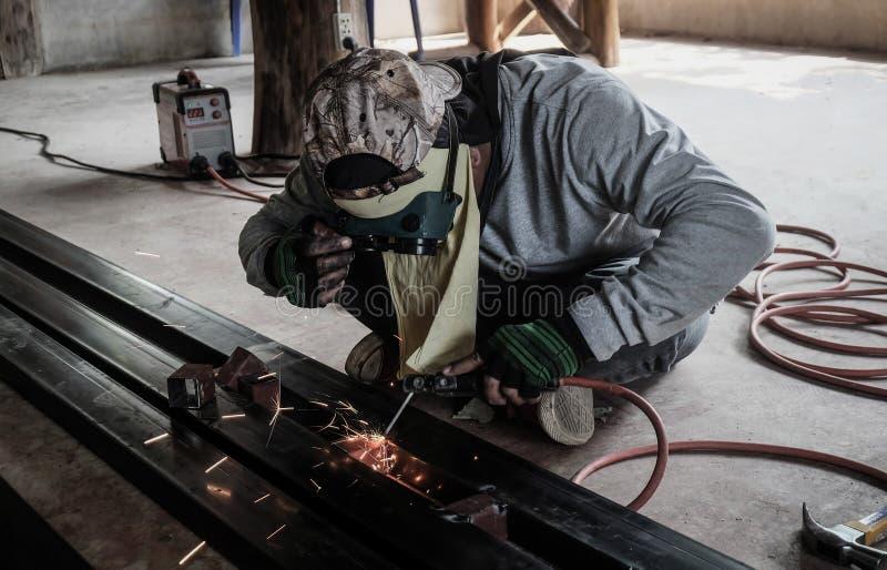 Trabajador industrial en el primer de la soldadura de la f?brica Rueda el?ctrica que muele en la estructura de acero en f?brica fotografía de archivo libre de regalías