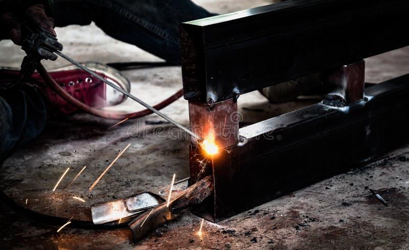 Trabajador industrial en el primer de la soldadura de la f?brica Rueda el?ctrica que muele en la estructura de acero en f?brica imágenes de archivo libres de regalías