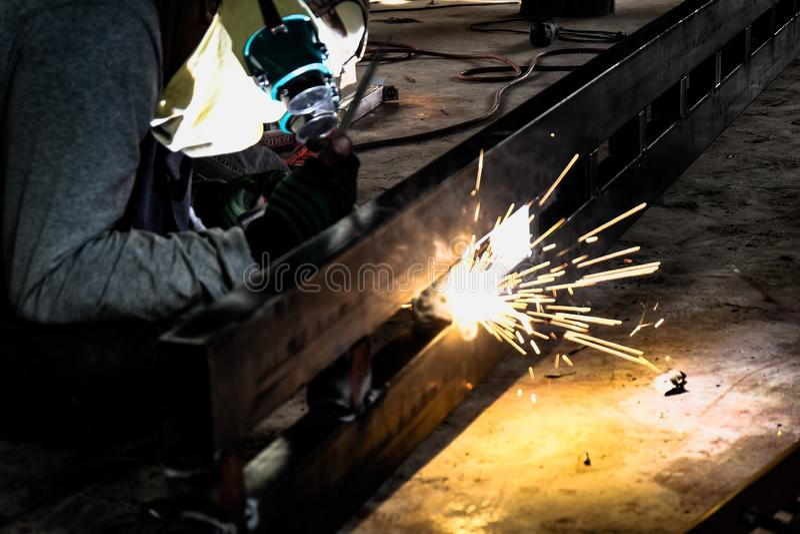 Trabajador industrial en el primer de la soldadura de la f?brica Rueda el?ctrica que muele en la estructura de acero en f?brica imagen de archivo libre de regalías