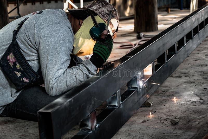 Trabajador industrial en el primer de la soldadura de la f?brica Rueda el?ctrica que muele en la estructura de acero en f?brica foto de archivo