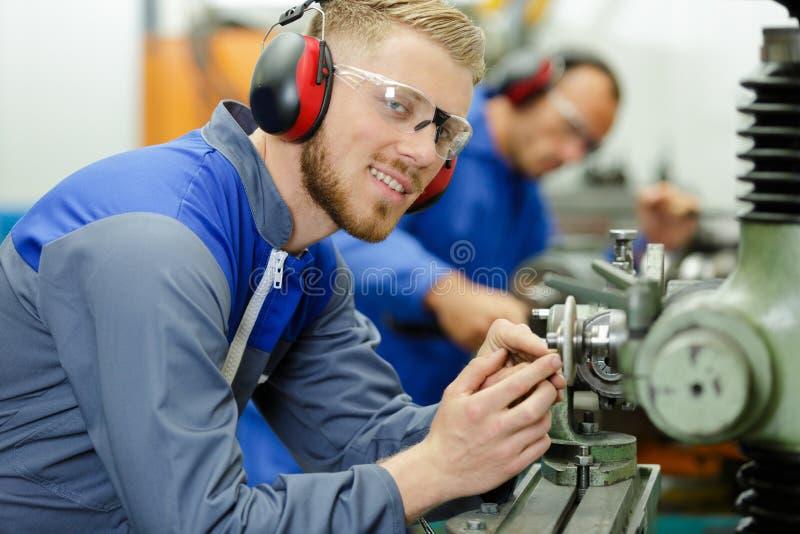 Trabajador industrial que examina el pedazo del trabajo foto de archivo