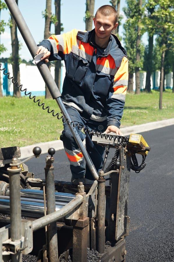 Trabajador joven de la pavimentadora en el asfaltado foto de archivo