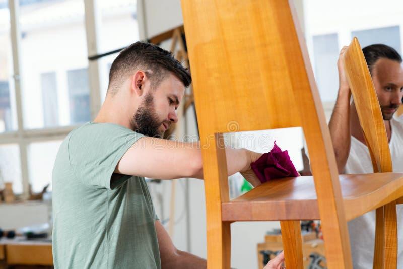 Trabajador joven en un taller de los carpinteros con la silla de madera imágenes de archivo libres de regalías