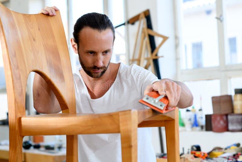 Trabajador joven en un taller de los carpinteros con la silla de madera foto de archivo