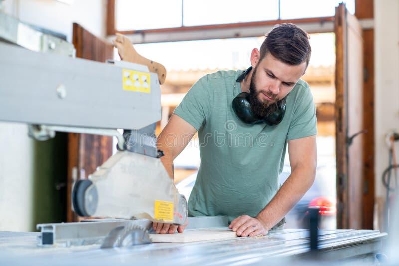 Trabajador joven en un taller de los carpinteros usando la sierra foto de archivo libre de regalías