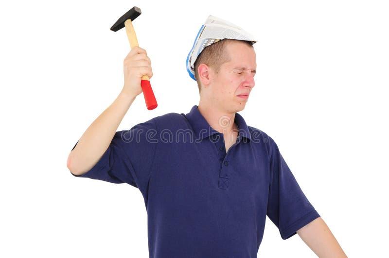 Trabajador joven que clava con el martillo foto de archivo
