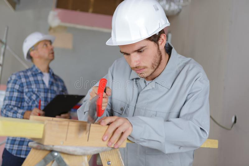 Trabajador joven que usa al colega mayor del handsaw que evalúa el sitio fotografía de archivo libre de regalías
