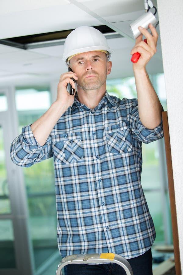 Trabajador listo para instalar la cámara CCTV imagenes de archivo